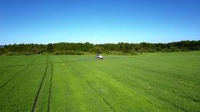 与洒拖拉机轨道和遥远的机器的绿色领域 股票视频
