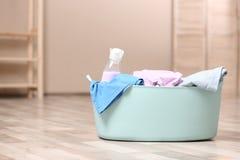 与洗涤剂和肮脏的衣裳的洗衣篮在户内地板上 库存图片