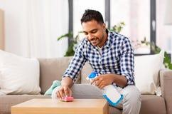 与洗涤剂的印度人清洁桌在家 免版税库存图片