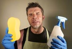 与洗涤剂被注重的浪花和海绵的年轻疲乏和沮丧的唯一人或家庭妇男清洁和用尽了如国内 免版税图库摄影