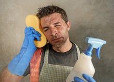 与洗涤剂被注重的浪花和海绵的年轻疲乏和沮丧的唯一人或家庭妇男清洁和用尽了如国内 库存图片
