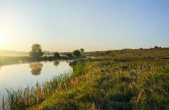 与流动在美丽的青山、领域和草甸之间的河的晴朗的夏天风景 库存图片