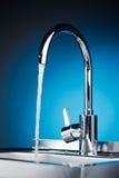 与流动的水的明三联式浴缸水嘴 库存照片