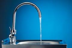 与流动的水的明三联式浴缸水嘴 免版税库存照片