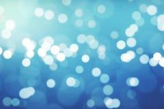 与流动的bokeh,欢乐假日新年好的圣诞节梯度蓝色背景 库存照片