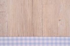 与浅兰的检查的布料在木背景 免版税图库摄影