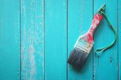 与浅兰的油漆的刷子在轻的木背景木头痛苦 免版税库存照片