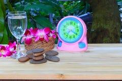 与浅景深的水玻璃凉快的精选的焦点 兰花紫色和石在木台面厚木板温泉概念 免版税库存照片