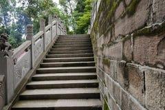 与浅浮雕的石楼梯栏杆和雕塑在夏天森林 免版税库存图片