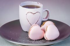 与浅粉红色的茶杯的桃红色心脏macarons在板材和奶油背景 免版税库存图片