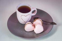 与浅粉红色的茶杯的桃红色心脏macarons在板材和奶油背景 库存图片