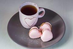 与浅粉红色的茶杯的桃红色心脏macarons在板材和奶油背景 免版税库存照片