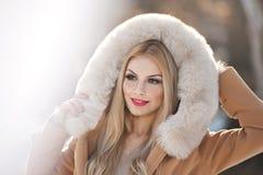 与浅褐色的皮大衣敞篷的可爱的年轻白种人成人 有佩带毛皮的华美的眼睛的美丽的白肤金发的女孩,户外 图库摄影