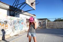 与浅顶软呢帽帽子的女孩时尚在他的在都市场面的头 免版税库存图片