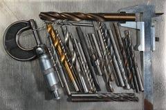 与测微表的在金属背景的钻头和轮尺 免版税库存照片