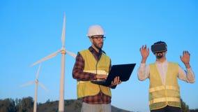 与测试虚拟现实玻璃的两位男性专家的风车领域 干净,环境友好的能量概念 股票视频