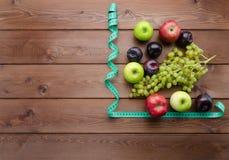 与测量的磁带和新鲜水果的饮食概念 库存图片