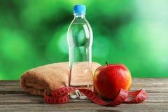 与测量的磁带和瓶的红色苹果在灰色木背景的水 库存图片