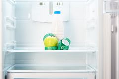 与测量的磁带和瓶的苹果计算机在冰箱架子  免版税库存照片