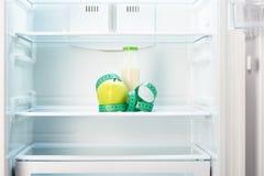 与测量的磁带和瓶的苹果计算机在冰箱架子  图库摄影