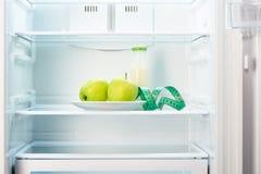 与测量的磁带和玻璃瓶的两个苹果在冰箱 免版税库存照片