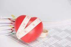 与测量的磁带的红色心脏在作为背景的财务帐户 免版税库存图片