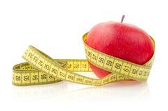 与测量的磁带的红色苹果计算机 免版税库存照片