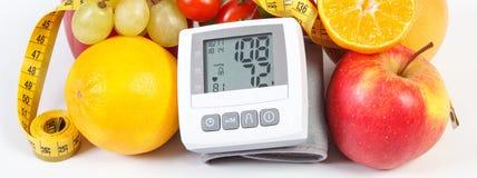 与测量的结果,新鲜的成熟果子与菜和厘米,健康生活方式的血压显示器 库存照片