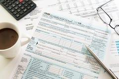 与浓咖啡杯子、计算器、玻璃和笔的收入税单形式在桌上 免版税库存照片