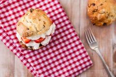 与浓奶油和果酱的可口新近地被烘烤的烤饼 免版税图库摄影