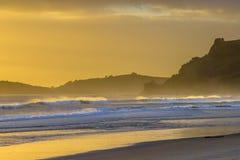 与浪花的海浪在Hauraki海湾的日落期间 免版税库存图片