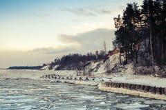 与浮动冰和冻码头的冬天沿海风景 免版税库存图片