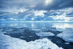与浮动熔化的冰片段的冬天沿海风景 免版税库存图片