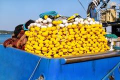 与浮游物的捕鱼网在蓝色小船的堆 库存照片