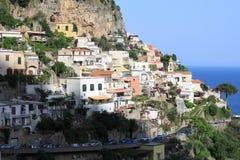与海、岩石和传统意大利建筑学的美好的风景在日落 库存照片