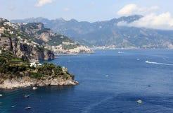 与海、岩石和传统意大利建筑学的美好的风景在日落 免版税库存照片