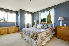与海军墙壁和大号床的卧室内部 免版税库存照片