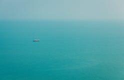 与海和一条风船的天际的美好的风景在海的镇静水域中下午 库存图片
