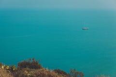 与海和一条风船的天际的美好的风景在海的镇静水域中下午 免版税库存图片