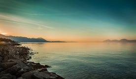 与海和小山的平安的风景在日出前 免版税库存照片