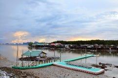 与海和山的日出在渔村Bangpat 库存图片