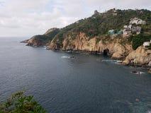 与海和峭壁的热带风景在阿卡普尔科,墨西哥传统地区  免版税库存照片
