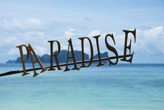 与海和海岛的天堂标志背景的 免版税库存照片