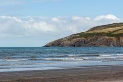与海和海滩的海湾风景在前景 免版税库存图片