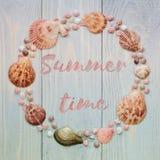 与海壳的夏时在蓝色木板条的背景和字法 库存图片