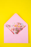 与海壳的桃红色信封在色的黄色背景,上面 库存图片