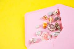 与海壳的桃红色信封在色的黄色背景,上面 免版税图库摄影