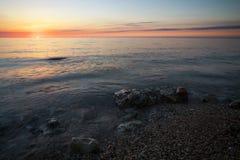 与海岸和日落天空的美好的风景 免版税库存照片