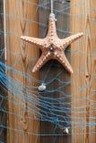 与海星的海星背景和在被风化的木材板条、设计和装饰的蓝色网 免版税图库摄影