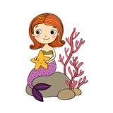 与海星的美丽的小的美人鱼坐石头 库存图片